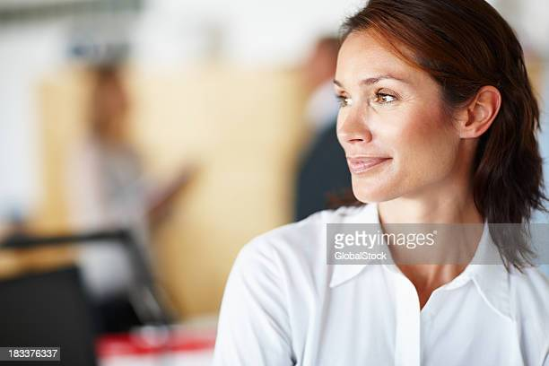 Portrait of thinking woman with coworkers in the background