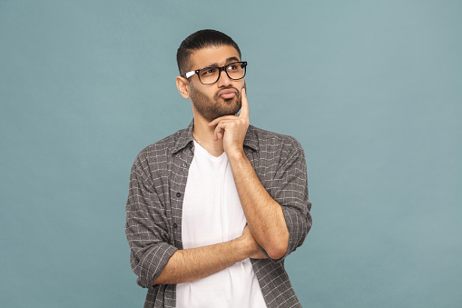 Portrait of thoughtful handsome man with black glasses in casual style thinking. 957333242