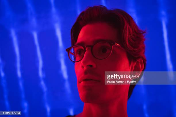 portrait of thoughtful young man looking away at night - museum fotografías e imágenes de stock