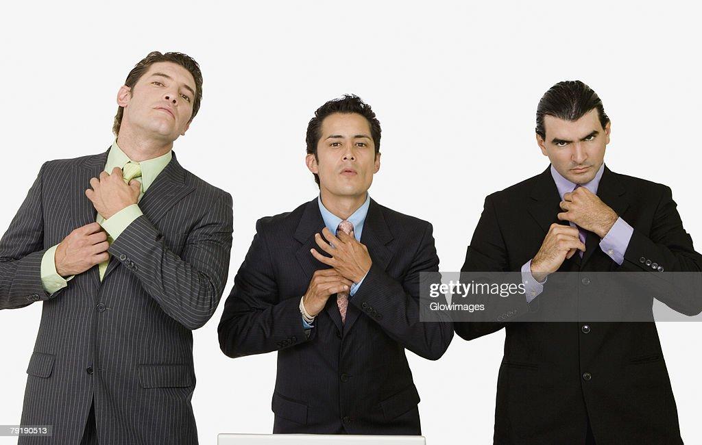 Portrait of three businessmen adjusting their ties : Foto de stock