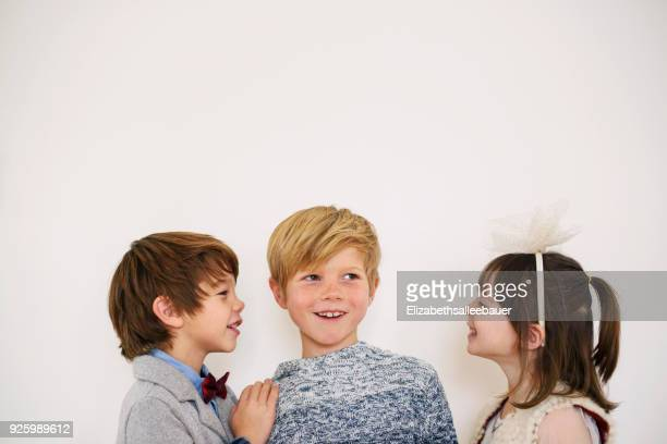 portrait of three children in smart clothing smiling - side by side stock photos and pictures