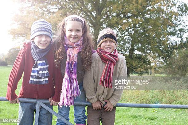 Portrait of three children leaning on fence, smiling