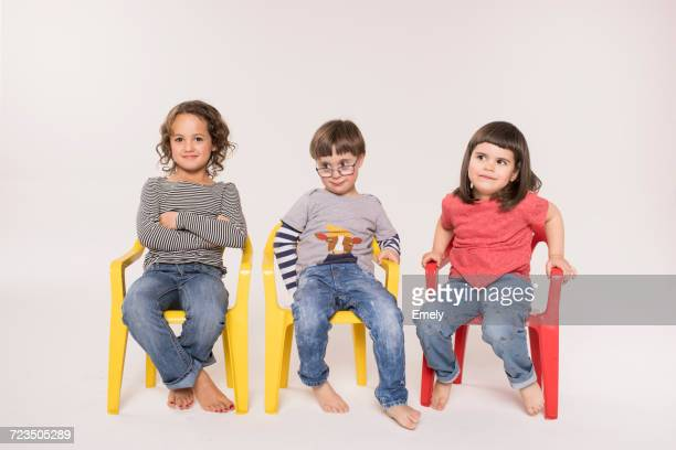portrait of three children sitting in colourful chairs, studio shot - sitzen stock-fotos und bilder