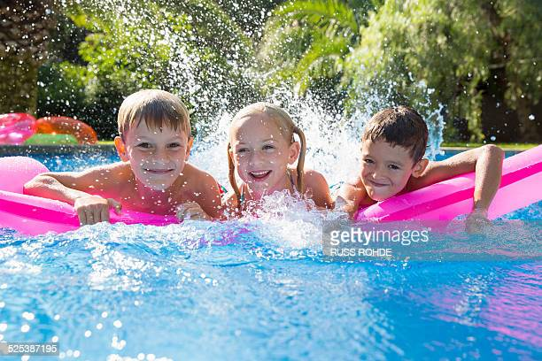 portrait of three children splashing on inflatable mattress in garden swimming pool - 6 7 años fotografías e imágenes de stock