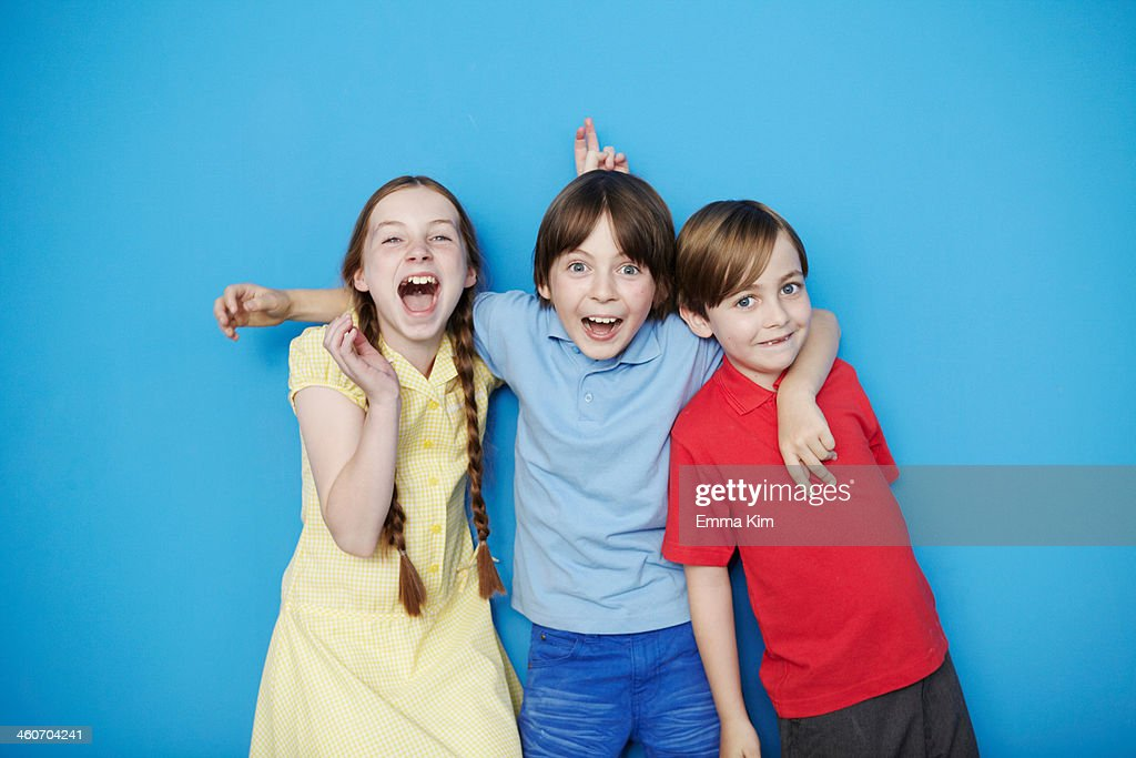 Portrait of three children with arms around each other against blue background : Stock Photo