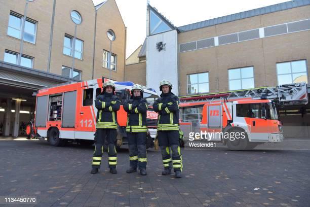 portrait of three confident firefighters standing on yard in front of fire engine - kleine personengruppe stock-fotos und bilder