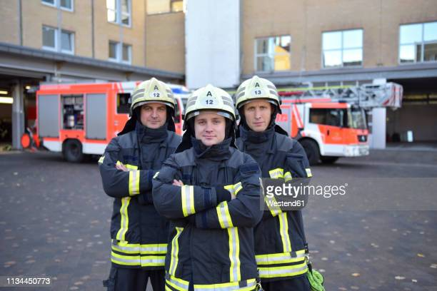 portrait of three confident firefighters standing on yard in front of fire engine - 救助隊 ストックフォトと画像