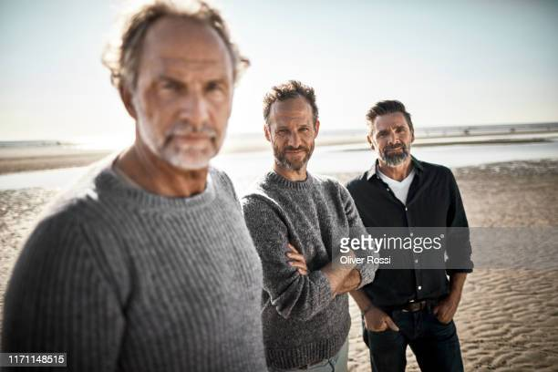 portrait of three confident men on the beach - drei personen stock-fotos und bilder