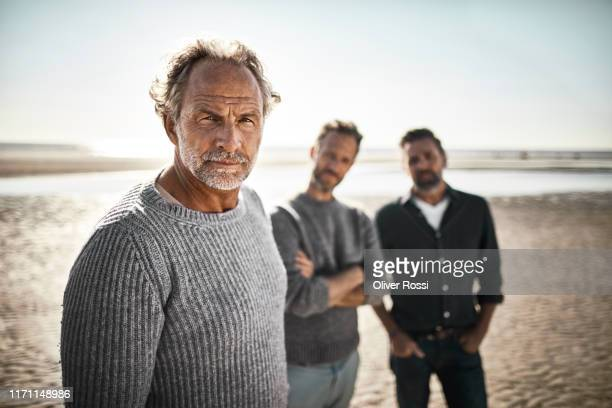 portrait of three confident men on the beach - 50 59 years stock pictures, royalty-free photos & images