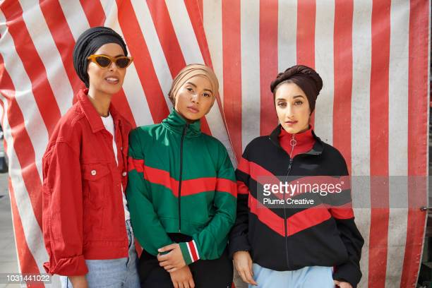 Portrait of three cool muslim women against striped background