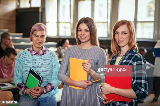 Portrait of three cute students in lecture hall