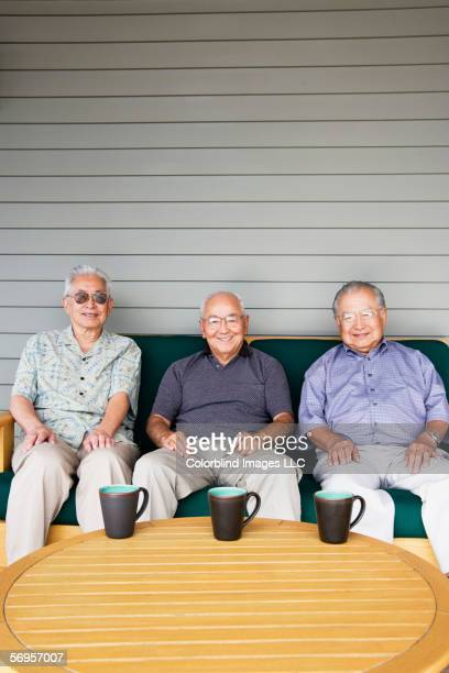 portrait of three elderly men sitting on couch drinking coffee - only senior men stock pictures, royalty-free photos & images