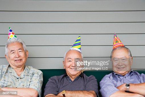 Portrait of three elderly men sitting on couch wearing birthday hats