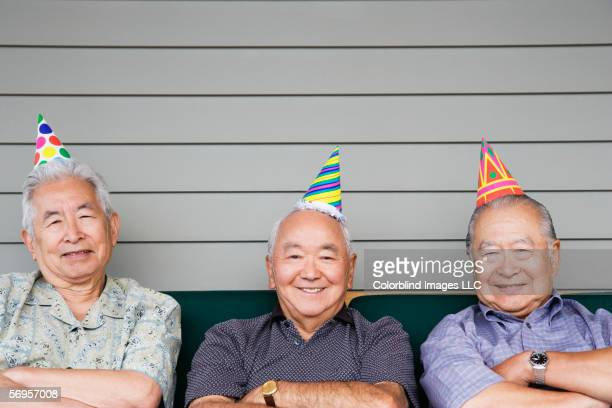 Portrait of three elderly men sitting on couch wearing birthday hats