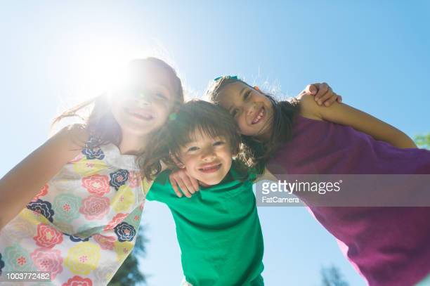 Portrait of three elementary-age kids posing on a hot summer day