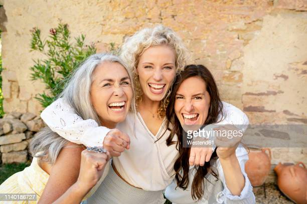 portrait of three excited women of different age embracing and cheering - tres personas fotografías e imágenes de stock