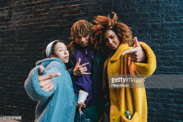 portrait of three friends against a black bricks wall, making gestures in front of the camera - rap stock pictures, royalty-free photos & images