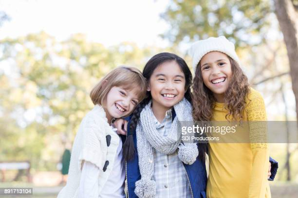 Portrait of three friends embracing outside for camera