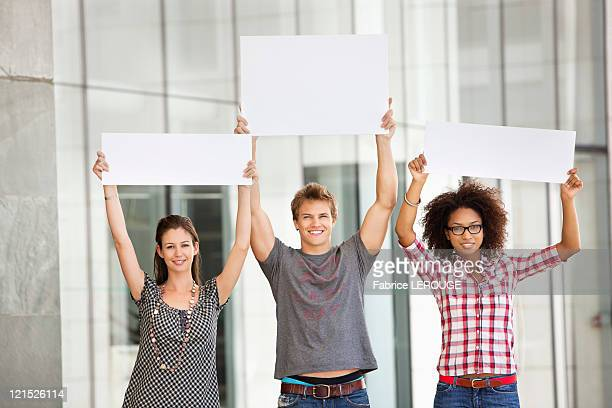 Portrait of three friends holding blank placards
