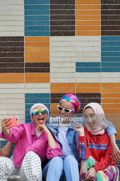 Portrait of three friends sitting in front of coloured tiled wall