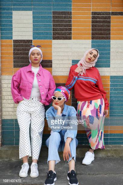 Portrait of three friends standing in front of coloured tiled wall