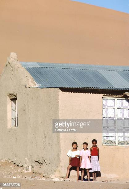 Portrait of three girls as they stand against the wall of a house in the Kalahari Desert South Africa 1985