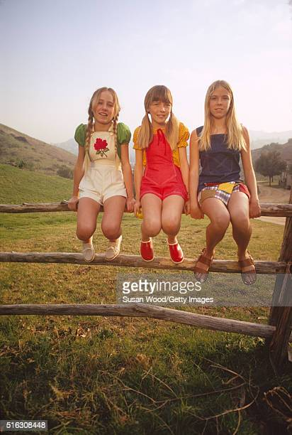 Portrait of three girls dressed in brightly colored or patchwork rompers as they pose on a splitrail fence in the the Hollywood Hills Los Angeles...