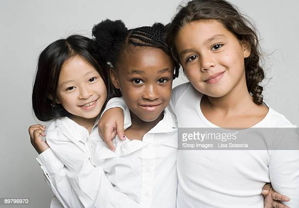 portrait of three girls embracing each other - nur kinder stock-fotos und bilder