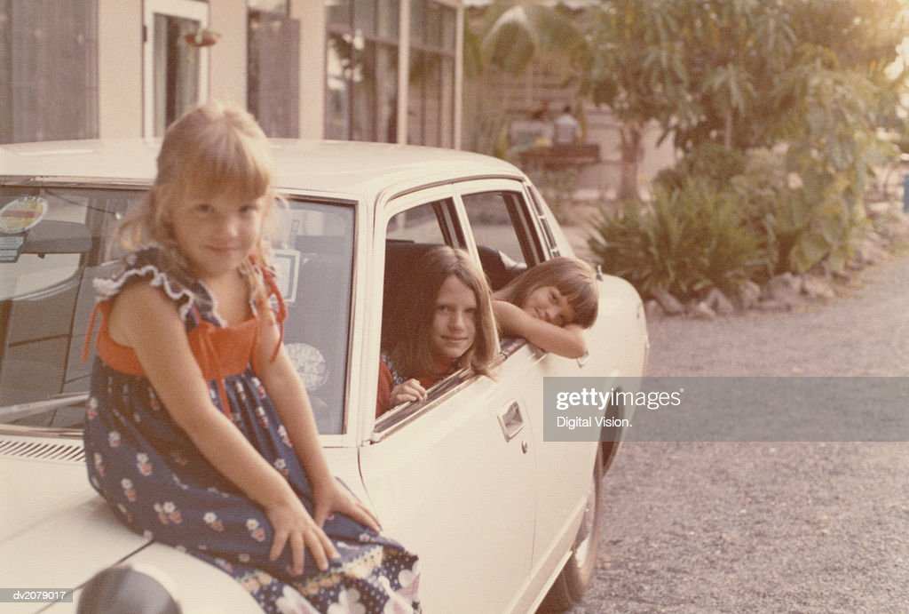 Portrait of Three Girls, One Sitting on a Car Bonnet, Two Others Inside the Car : Stock Photo