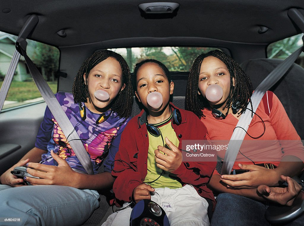 Portrait Of Three Girls Sitting At The Back Of A Car And Chewing Gum ...