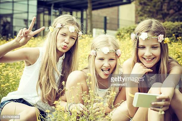 Portrait of three girls wearing floral wreaths taking a selfie on a flower meadow
