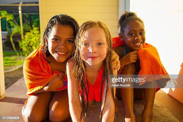 portrait of three girls wrapped in towel on porch - tween girls hot stock photos and pictures