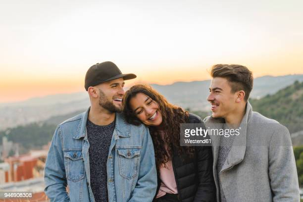portrait of three happy friends on a hill at sunset - tres personas fotografías e imágenes de stock