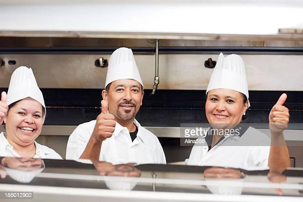 Portrait of three happy smiling chefs inside the restaurant kitchen