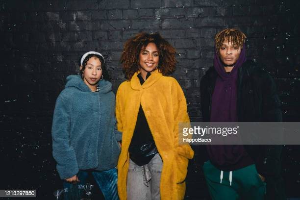 portrait of three hip friends together against a black bricks wall - rapper stock pictures, royalty-free photos & images