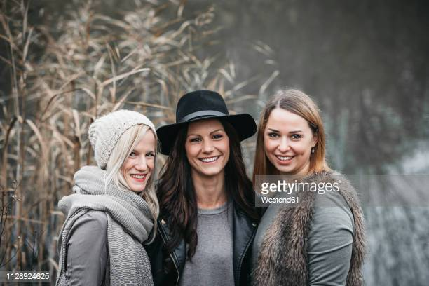 Portrait of three laughing friends in autumnal nature