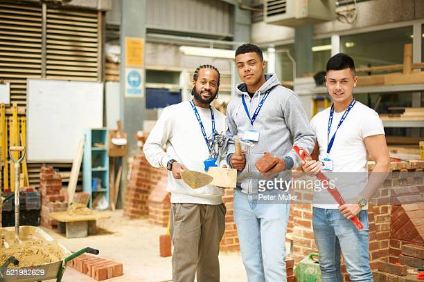 Portrait of three male college students in bricklaying workshop