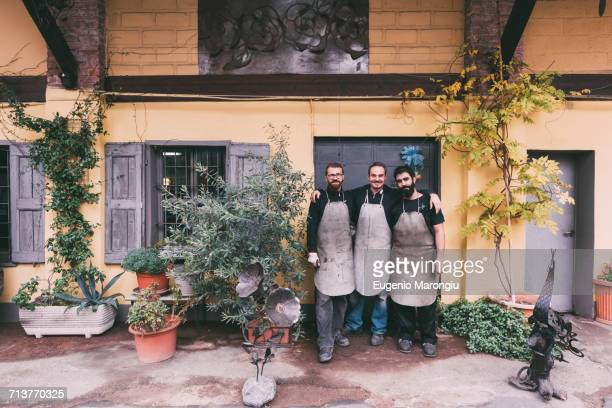 Portrait of three male metalworkers outside forge