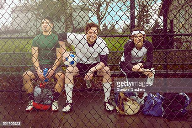Portrait of three male soccer players sitting behind wire fence