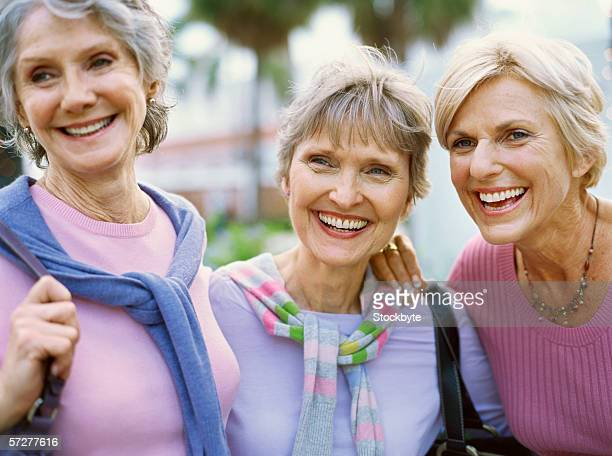 portrait of three mature women smiling - purple shirt stock photos and pictures