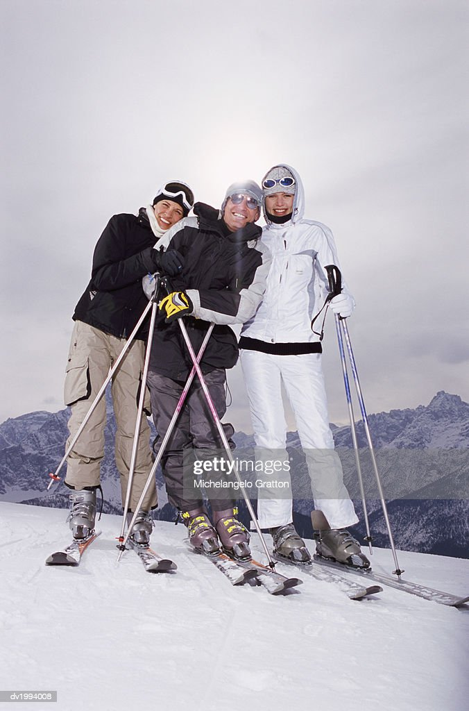Portrait of Three People Standing on a Ski Slope With Their Skis and Ski Poles : Stock Photo