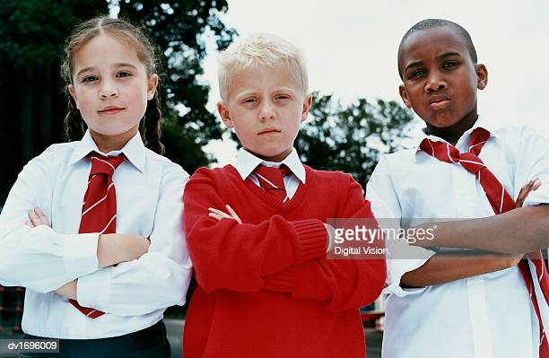 Portrait of Three Primary School Children Standing With Their Arms Folded, Scowling at the Camera