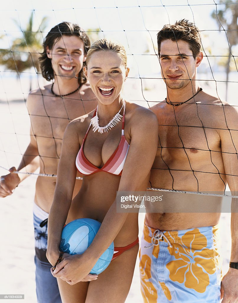 Portrait of Three Smiling, Young Adults Standing by a Volleyball Net on a Beach : Stock Photo