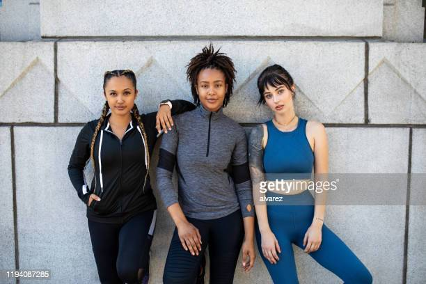 portrait of three sports women standing together - female friendship stock pictures, royalty-free photos & images