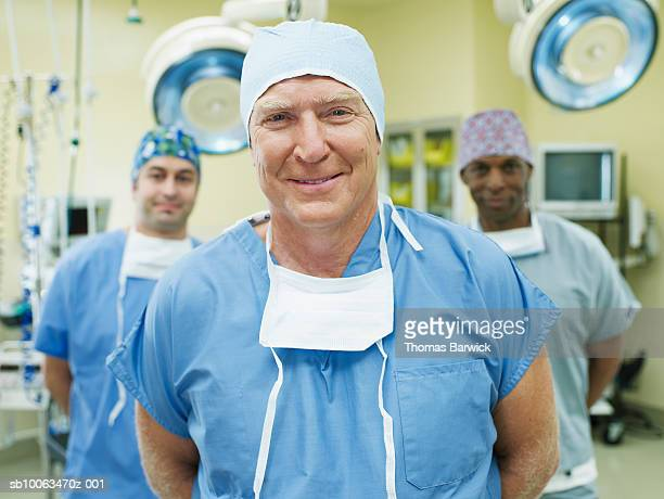Portrait of three surgeons in operation room, smiling (focus on foreground)