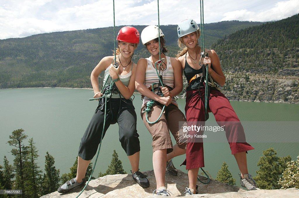 Portrait Of Three Teenage Rock Climbing Hanging On Ropes ...