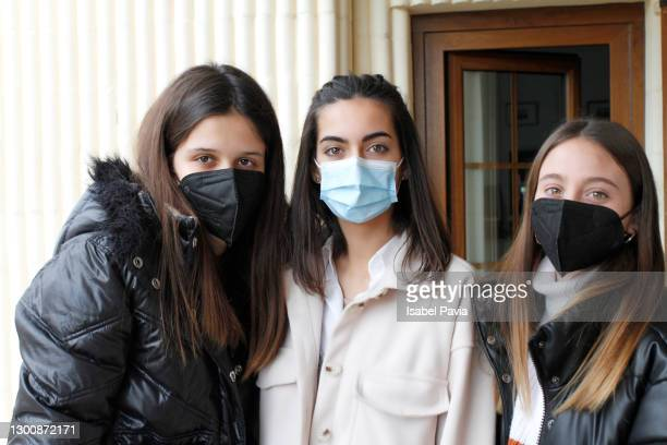 portrait of three teenagers wearing protective face masks. new normal concept. - covid 19ワクチン ストックフォトと画像