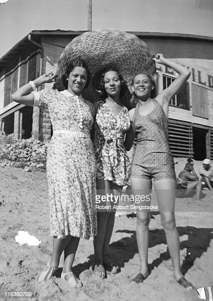 Portrait of three unidentified women as under a very large straw hat they pose on the beach outside the Idlewild Club House Idlewild Michigan...