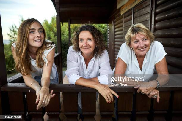 portrait of three women leaning on balcony of a log cabin - two generation family stock pictures, royalty-free photos & images