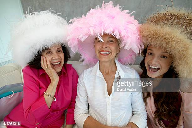 portrait of three women sitting on a sofa wearing big feather hats and laughing - evening wear stock pictures, royalty-free photos & images